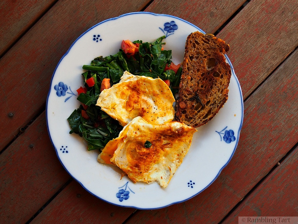 fried eggs on greens and tomatoes
